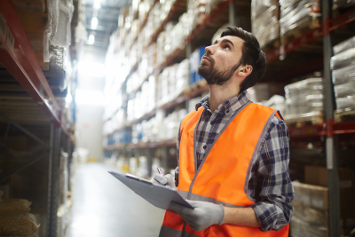 warehouse worker looking up the tall shelves doing inventory control
